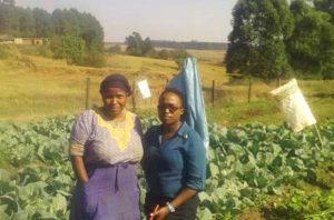 Busisiwe med EDT-medarbetaren Gugu Dludlu i hennes odling med hemmet i bakgrunden